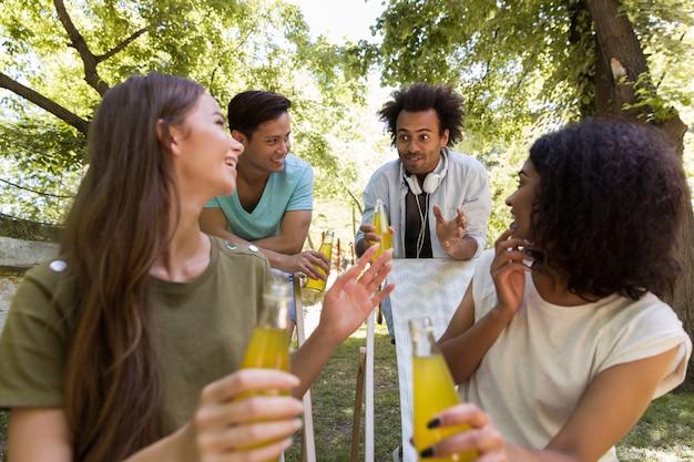 Alegres jóvenes amigos multiétnicos estudiantes afuera bebiendo jugo