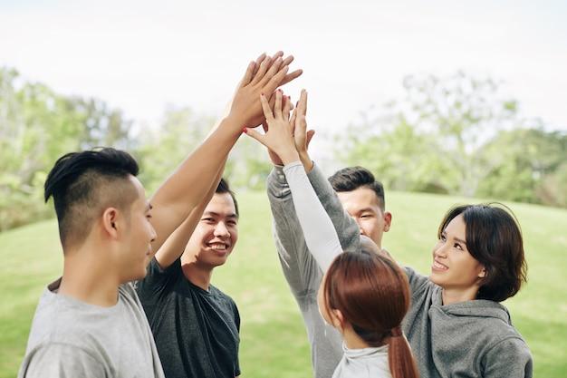 Alegres jóvenes asiáticos dándose cinco después de terminar el entrenamiento al aire libre