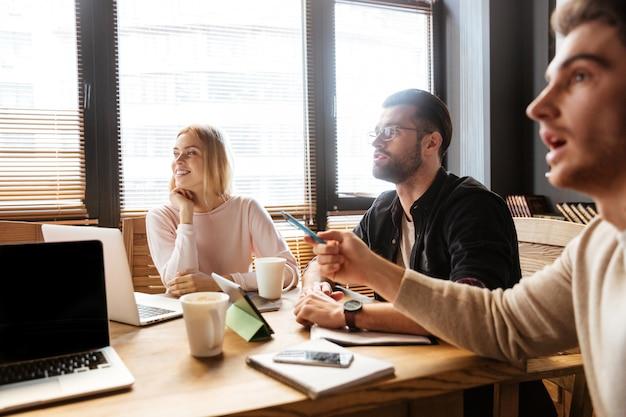 Alegres jóvenes colegas sentados en la oficina