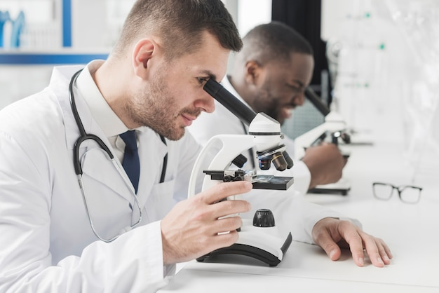 Alegres médicos multirraciales con microscopios