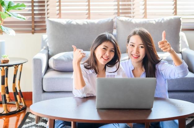 Alegres mujeres asiáticas usando una computadora portátil juntas