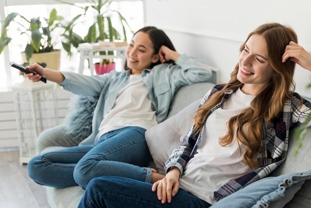 Alegres mujeres jóvenes viendo la tele
