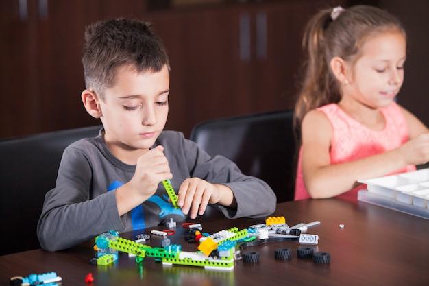 Alegres niños sonrientes están construyendo un constructor.
