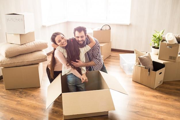 Alegres padres jóvenes están abrazando a su hija juntos. la han encontrado en una caja. ella se escondió allí. la familia se acaba de mudar a un nuevo departamento y tiene que desempacar todos los que tienen en caja.