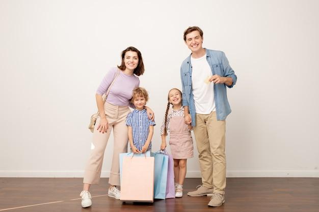 Alegres padres jóvenes y sus dos hijos con bolsas de papel mirándote después de visitar la venta del viernes negro en el centro comercial