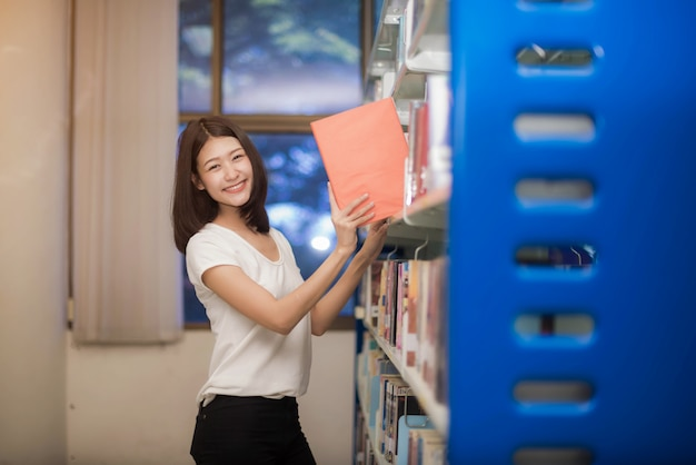 Alegres universitarios con feliz leen un libro e informe en la biblioteca.