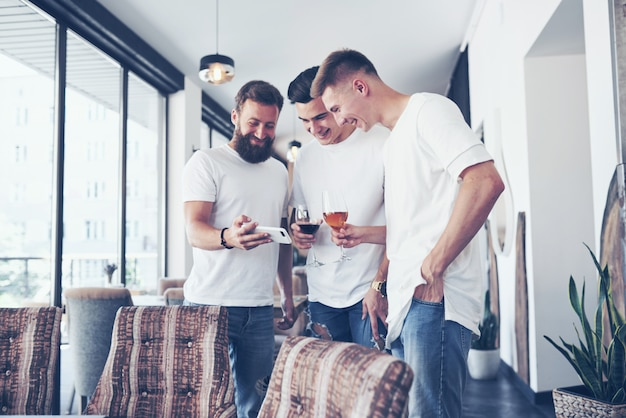 Alegres viejos amigos se comunican entre ellos y miran por teléfono, con vasos de whisky o vino en el pub. concepto de entretenimiento y estilo de vida. wifi conectado a personas en la mesa de bar