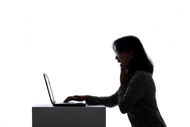 Alegría asiática de la mujer mientras que usa un ordenador portátil.