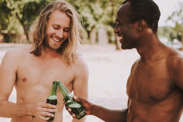 Alegría feliz de los hombres con las botellas de cerveza en la playa.