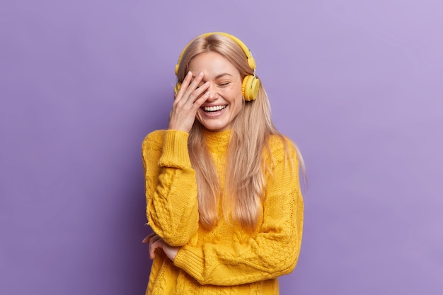 Alegría joven europea con cabello rubio se ríe a carcajadas hace que la cara de la palma escuche música a través de auriculares inalámbricos viste un suéter amarillo informal