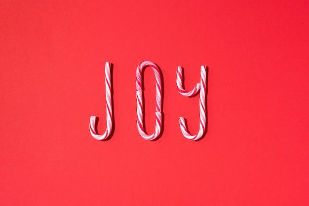 Alegría palabra escrita con bastones de caramelo de navidad sobre fondo rojo.