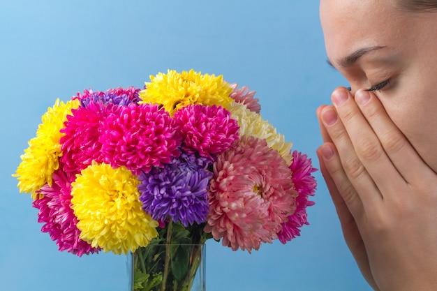 La alergia a las flores florece y al polen. mujer y flores sobre un fondo azul