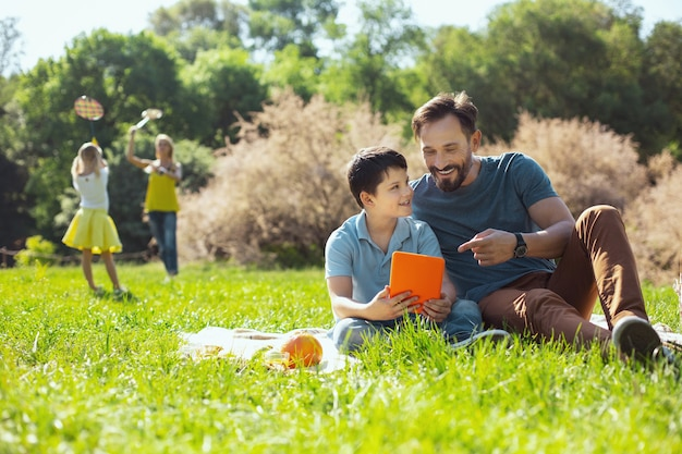 Alerta muchacho encantador sosteniendo una tableta con su padre en el parque