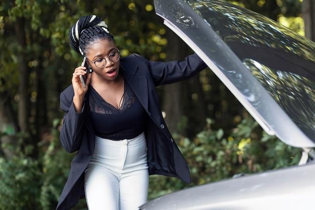 Alerta a mujer hablando por teléfono sobre el motor de su coche que no funciona