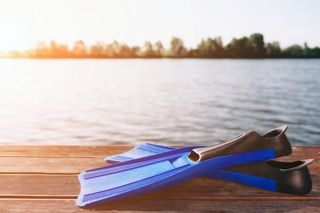 Aletas azules para nadar en la playa de arena. gran río o lago. el sol brilla. cielo despejado.