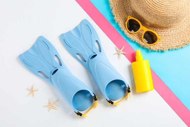 Aletas, gafas de sol, sombrero de paja, estrellas de mar y protector solar en la mesa de colores