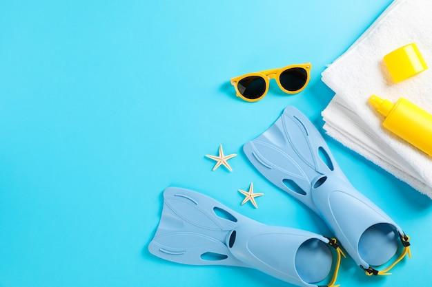 Aletas, gafas de sol, toalla y estrellas de mar en la mesa de colores