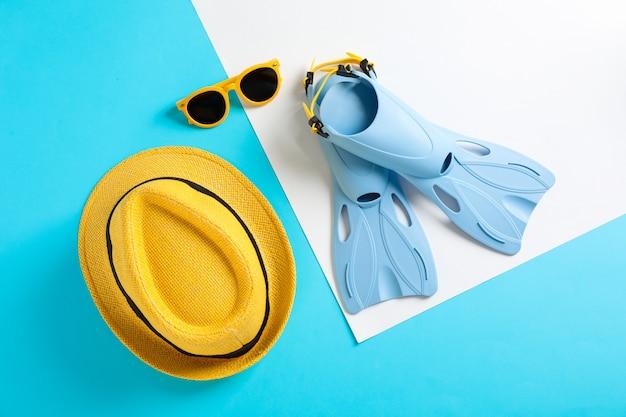 Aletas, gorro y gafas de sol en la mesa de color