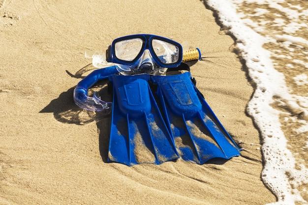 Aletas de natación azul, máscara, snorkel para practicar surf en la playa de arena. concepto de playa