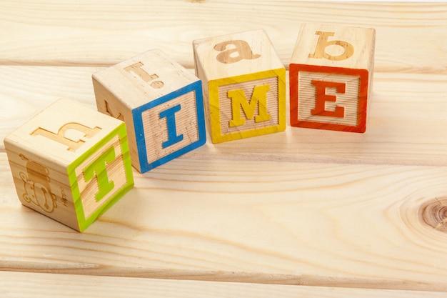 Alfabeto de bloques de madera sentar en el piso de madera. hora