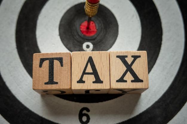 Alfabeto de impuestos en cubo de madera y destino para el concepto de retorno financiero