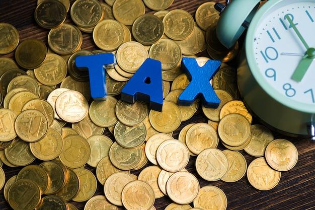 Alfabeto de impuestos con pila de monedas y despertador vintage en madera