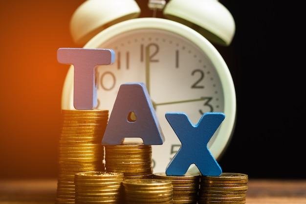 Alfabeto de impuestos con pila de monedas y despertador vintage