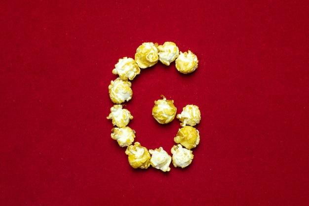 Alfabeto inglés del cine palomitas. letra g. fondo rojo para diseño.