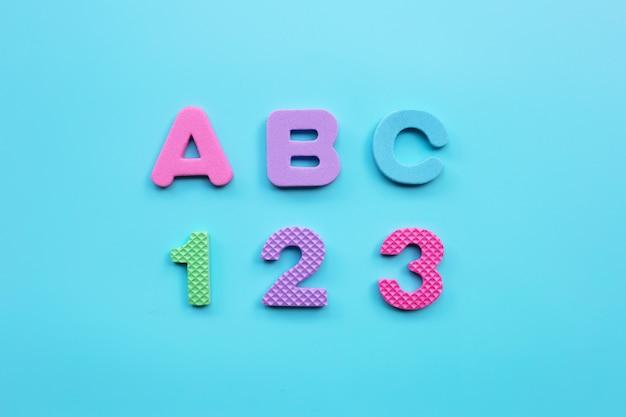 Alfabeto inglés y números sobre fondo azul. concepto de educación