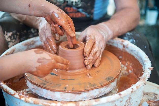 El alfarero hace platos de cerámica en torno de alfarero. el escultor en el taller hace el primer plano del producto de arcilla. manos del alfarero.