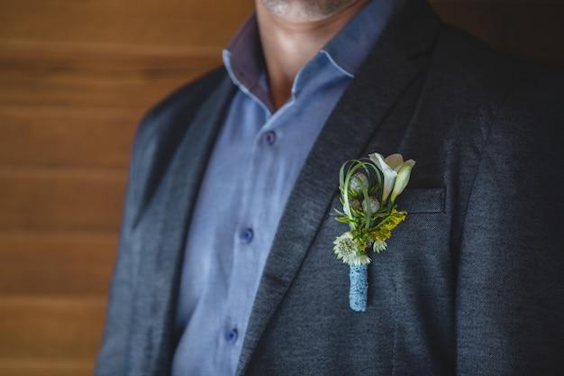 Un alfiler de flores de colores pastel de temporada en la chaqueta de un hombre.