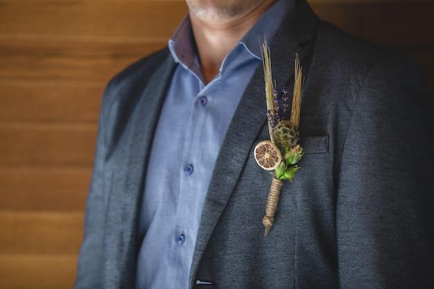 Un alfiler de flores ornamentales de navidad y rodaja de naranja en la chaqueta de un hombre.