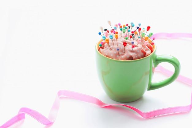 Alfileres multicolores para coser en una cama de agujas y cinta decorativa rosa.