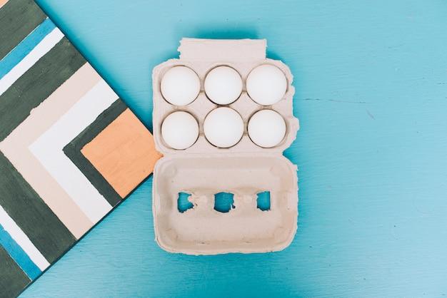 Alfombra y cartón de huevos sobre fondo azul