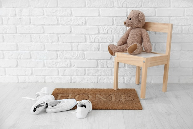 Alfombra de puerta, silla con juguetes y zapatos cerca de la pared de ladrillo