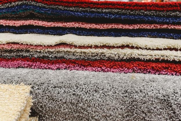 Alfombras de varios colores apiladas en un almacén.