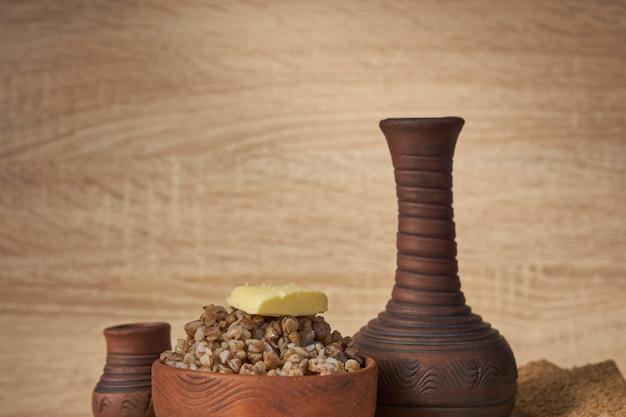 Alforfón cocido con una rodaja de mantequilla servido con patatas fritas de centeno en la mesa de madera.