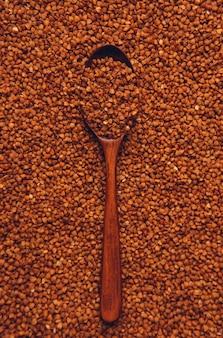 Alforfón en una cuchara de madera. vista superior, vertical