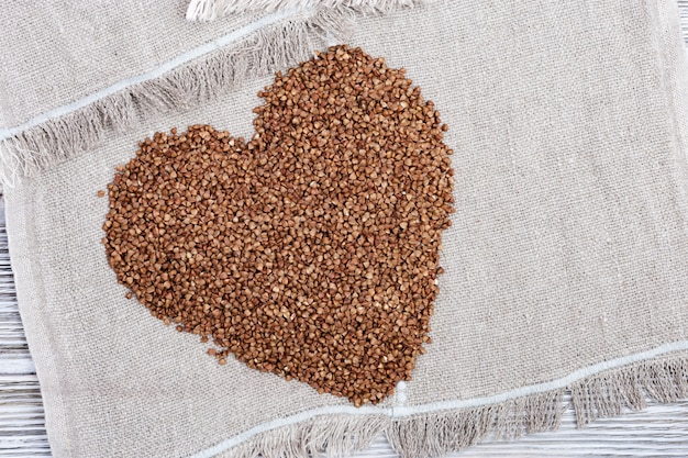 Alforfón tostado crudo en forma de corazón en madera clara. grechka rusa. alimentos orgánicos de dieta saludable.
