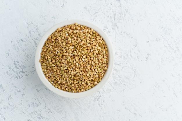 Alforfón verde en un tazón blanco sobre blanco. cereales secos en taza, comida vegana