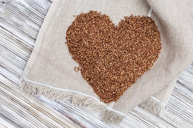 Alforfones esparcidos en forma de corazón en la mesa de madera con tela de saco.