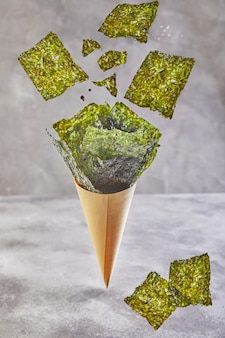 Alga nori crujiente que cae en una taza del cono en un fondo gris, levitación. comida japonesa nori. hojas secas de algas