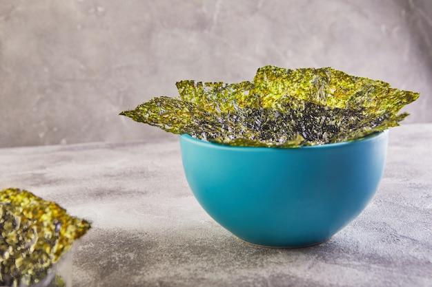 Alga nori crujiente en un recipiente azul sobre un fondo gris. comida japonesa nori. hojas secas de algas.