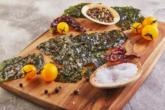 Alga nori crujiente con tomates cherry y especias en una tabla de madera sobre hormigón gris. comida japonesa nori. hojas secas de algas.