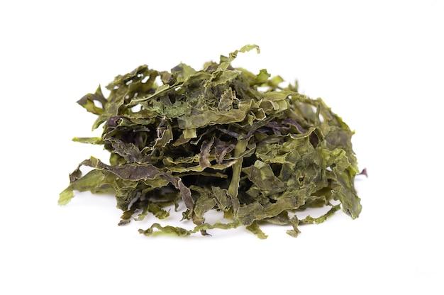 Alga wakame seca, aislada en blanco. col rizada, comida seca asiática.