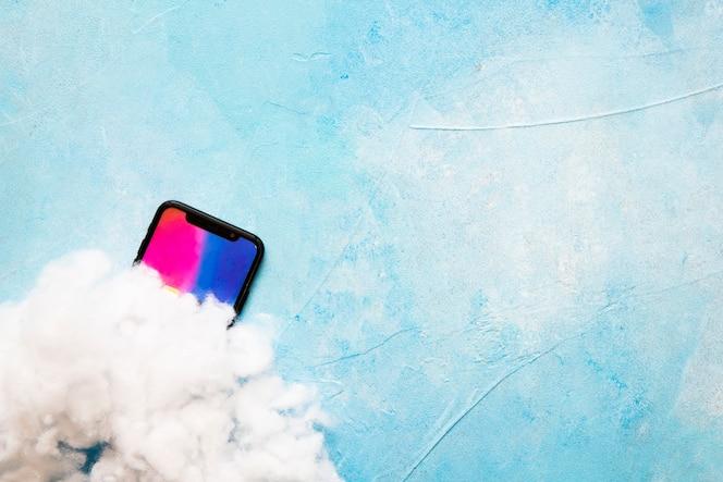 Algodón en la pantalla del teléfono móvil sobre fondo azul pintado
