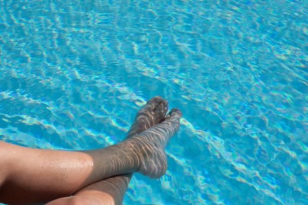 Alguien con los pies en la piscina.