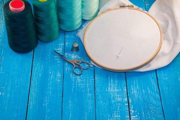 Algún hilo de color turquesa con la tela en el bastidor de bordado de madera para la costura