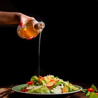 Alguna mujer que vierte el aceite en la ensalada deliciosa en una placa en el fondo de madera y negro, vista lateral. espacio para texto