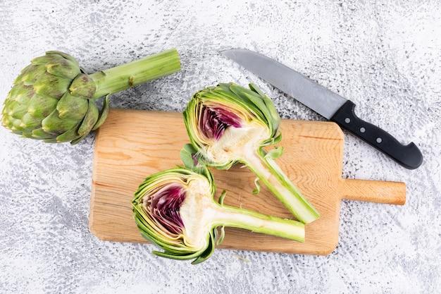 Algunas de alcachofas y rodajas con cuchillo en una tabla de cortar sobre fondo gris claro, vista superior.